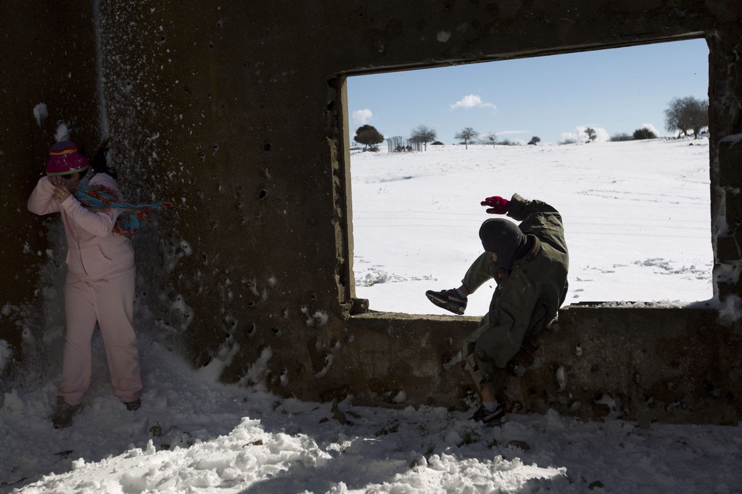 Jan. 10, 2013. Children play in an abandoned building at a snow covered field in the Golan Heights on the border with Syria.