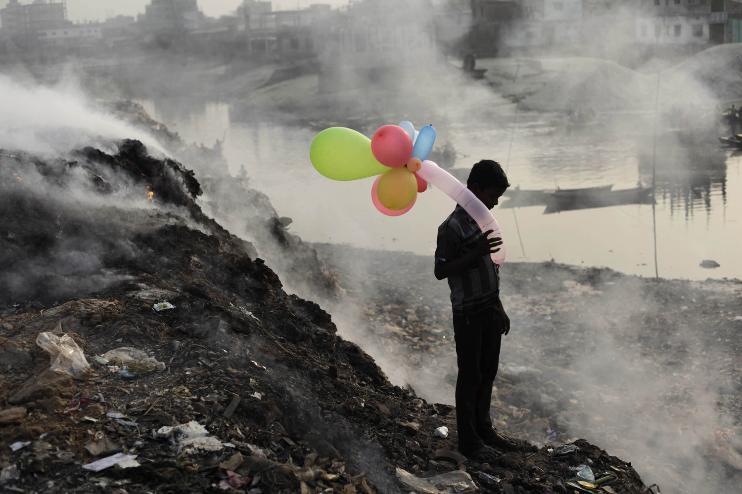 Jan. 19, 2013. A boy plays with balloons by Buriganga river as smoke emits from a dump yard during sunset in Dhaka, Bangladesh.