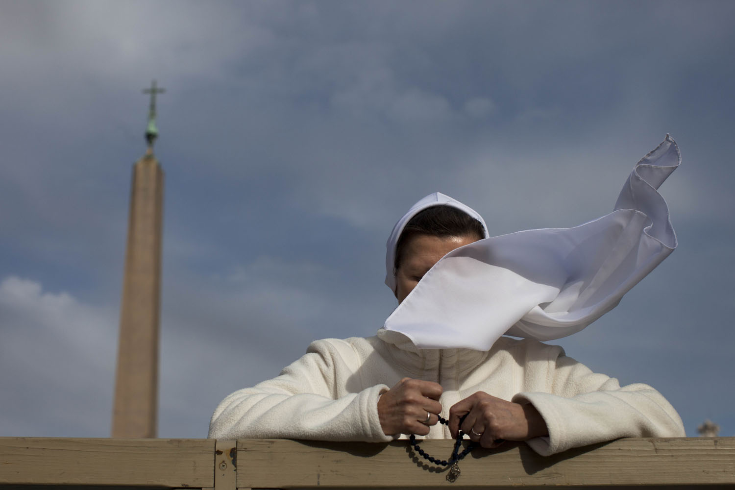 March 14, 2013. A gust of wind blows a nun's veil as she stands in front of St. Peter's Basilica, at the Vatican.
