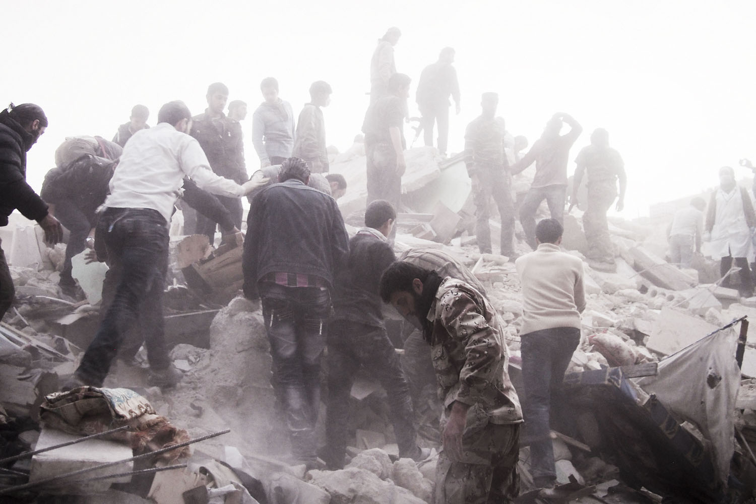 March 19, 2013. Searching for survivors among the rubble of a residential building targeted by a regime airstrike in the rebel-held Al-Sukri district in Aleppo, Syria.