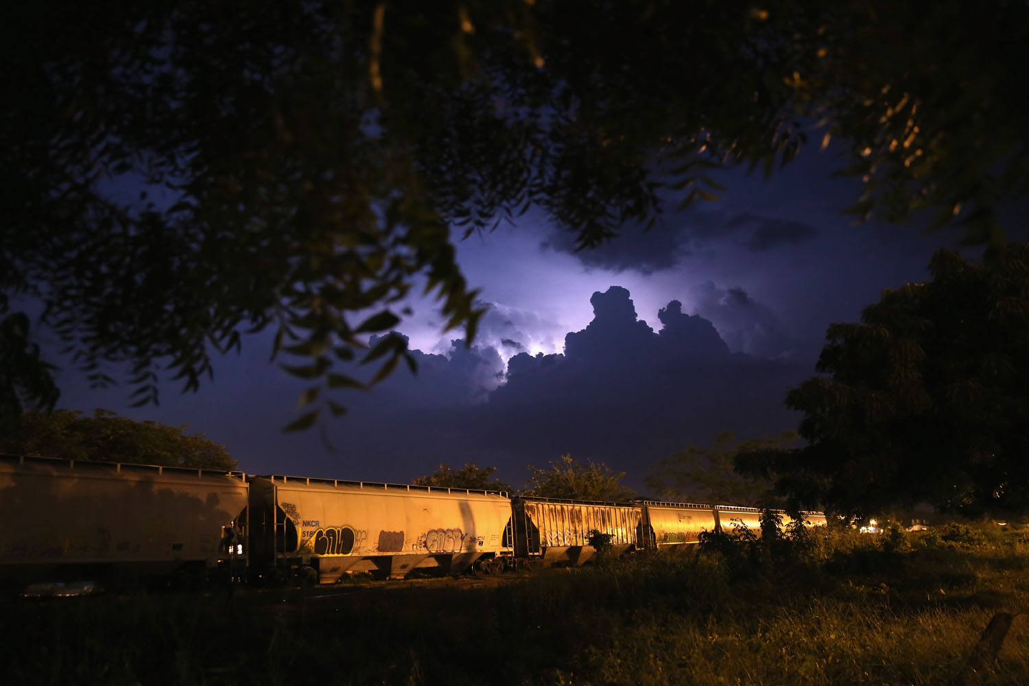 Aug. 3, 2013. Lightning flashes across the sky as a freight train known as  la bestia,  prepares to depart in Arriaga, Mexico.