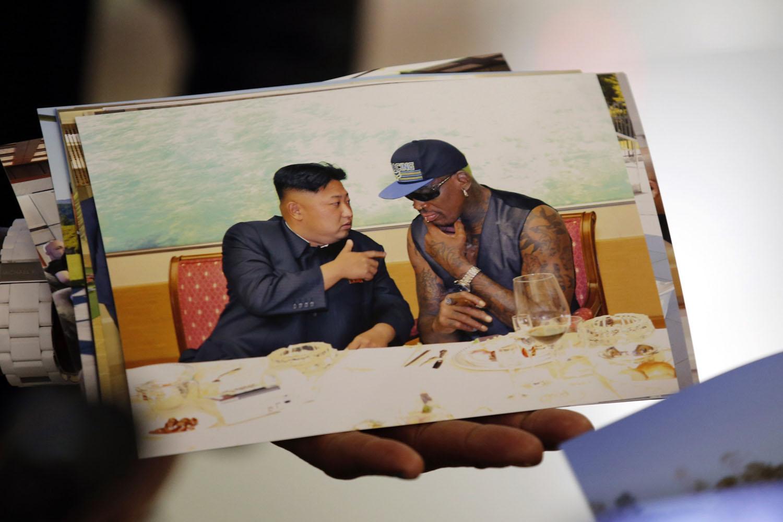 Sept. 7, 2013. Former basketball star Dennis Rodman displays a photograph he took with North Korean leader Kim Jong-un as he arrives at Beijing Capital International Airport.