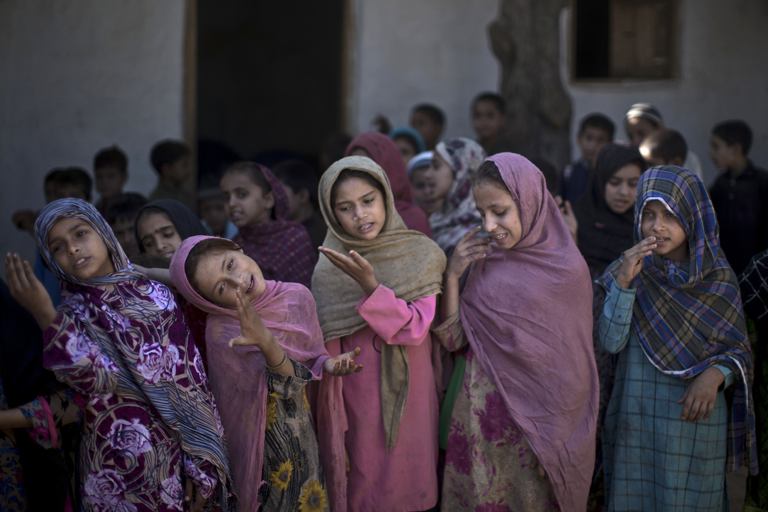 Oct. 14, 2013. Pakistani schoolgirls, who were displaced with their families from Pakistan's tribal areas due to fighting between the Taliban and the army, sing with their teacher before starting their classes, at their makeshift school on the outskirts of Islamabad.