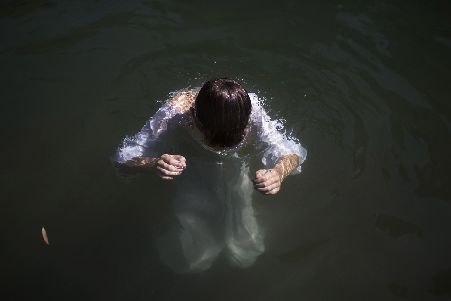 Oct. 16, 2013. A Christian pilgrim immerses himself in the waters of the Jordan River at Yardenit Baptismal Site near Tiberias in northern Israel.