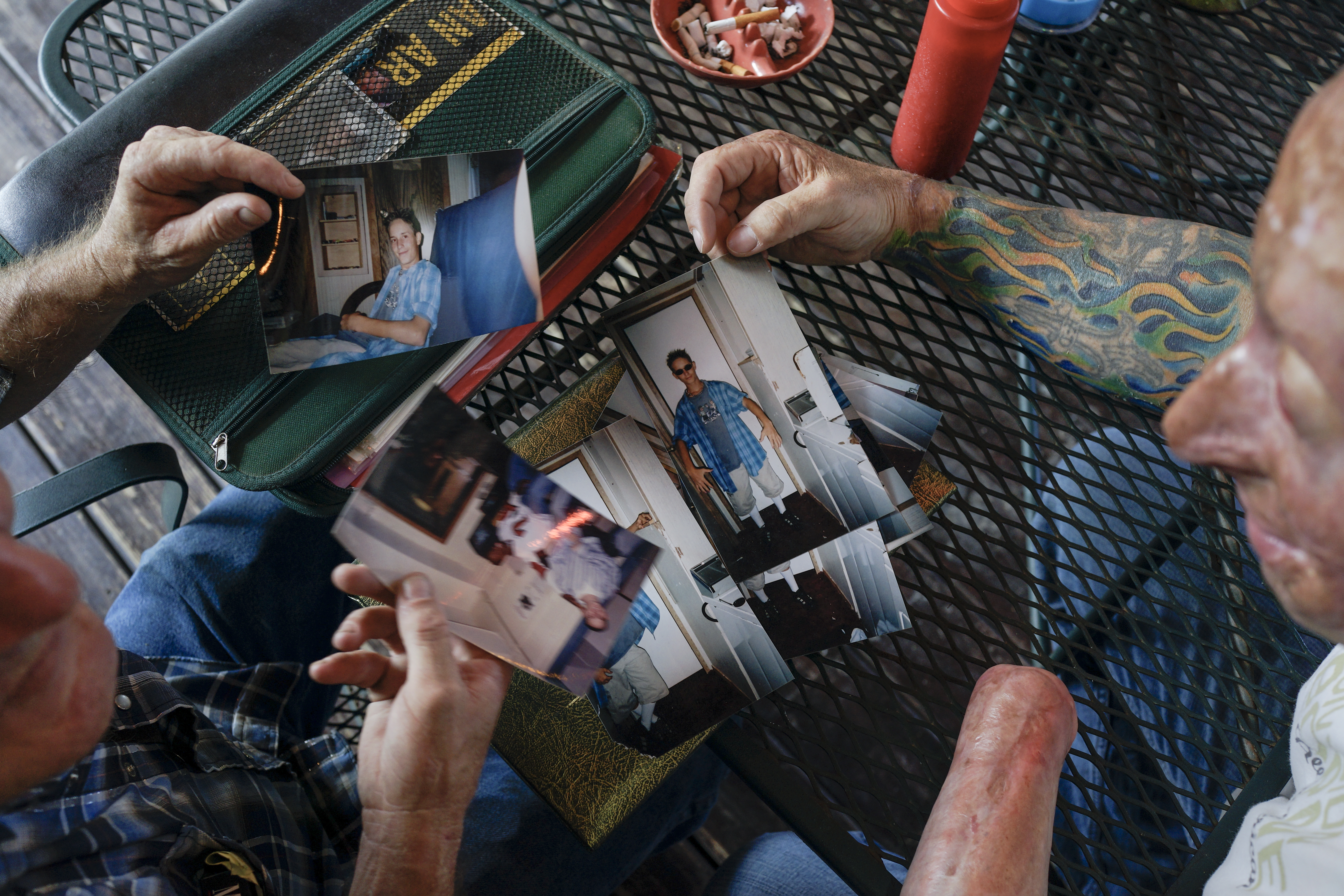 Bobby looks at pictures of Rodney McCandless with his father, Lynn, in Livingston, Texas, 2013.