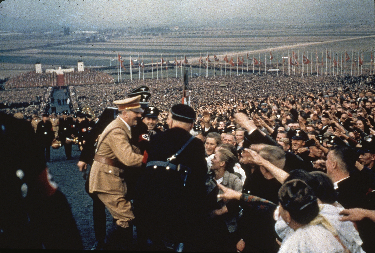 Adolf Hitler greets the cheering throng at a rally in 1937.