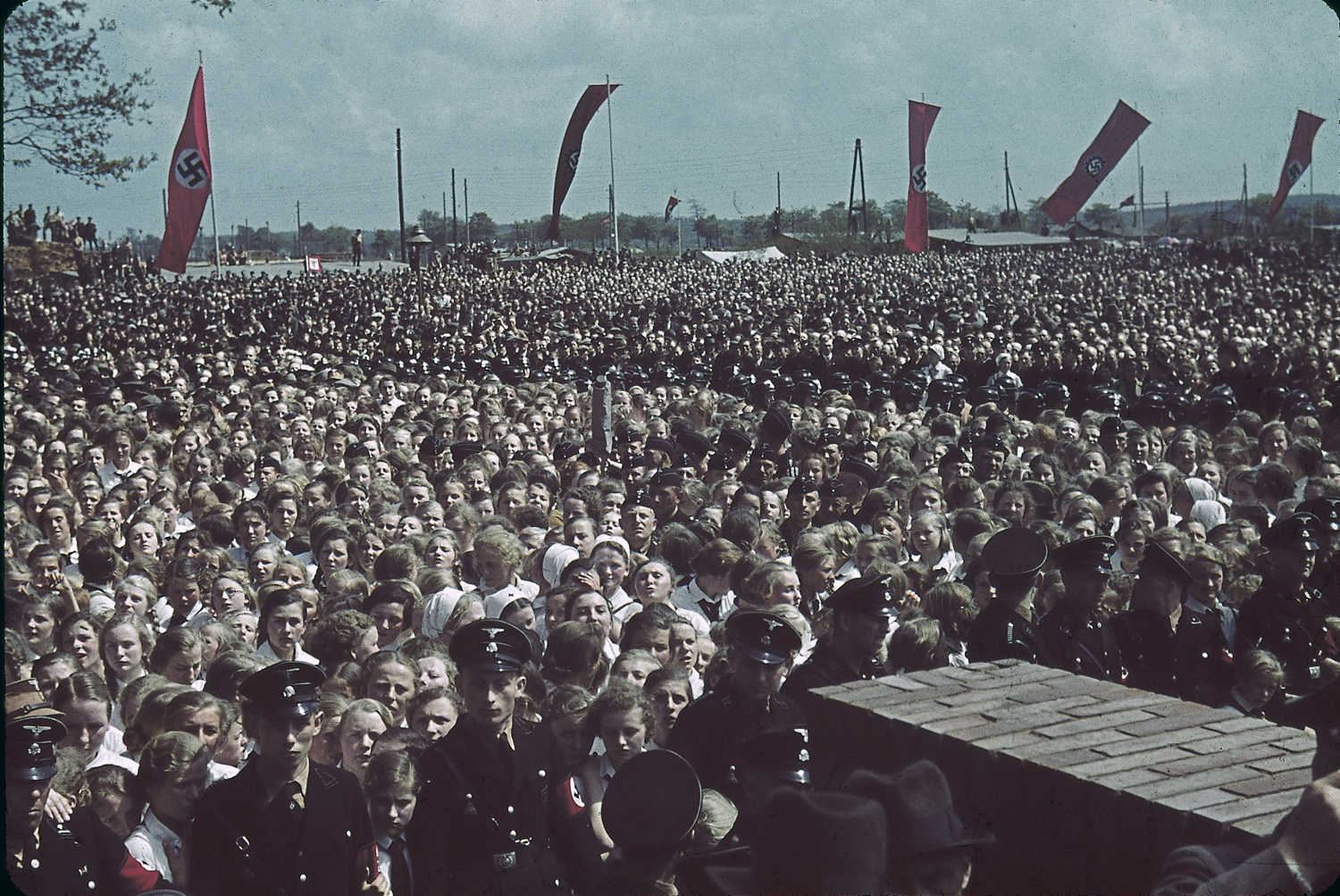 Crowds greet a saluting Adolf Hitler at a cornerstone ceremony at a Volkswagen factory, 1938.