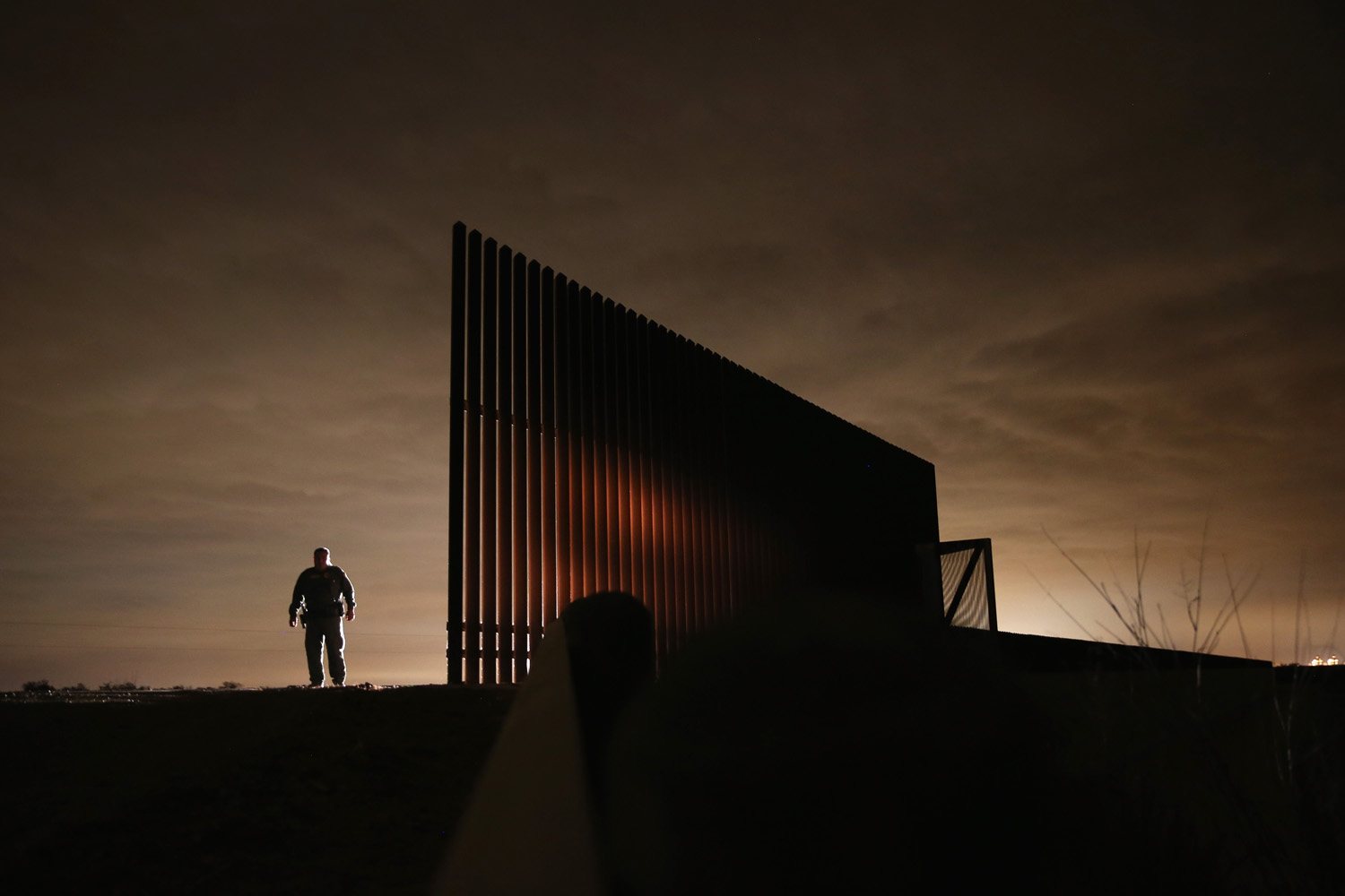 April 10, 2013. U.S. Border Patrol agent Sal De Leon stands near a section of the U.S.- Mexico border fence while stopping on patrol in La Joya, Texas.