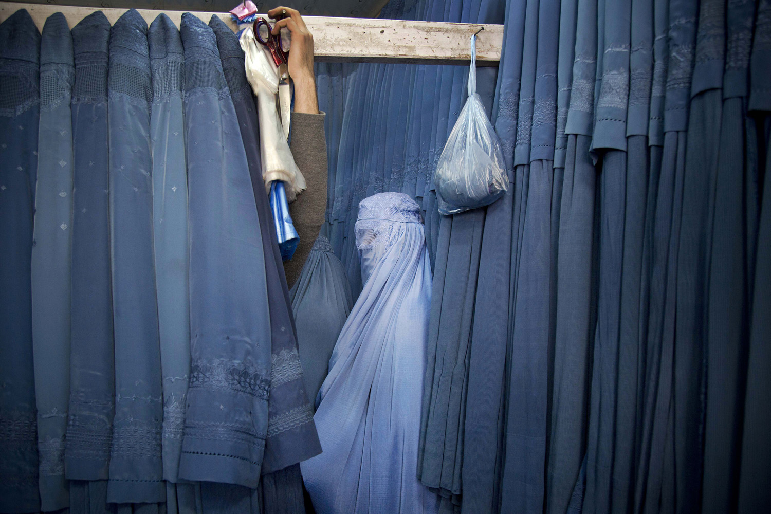 April 11, 2013. An Afghan woman waits in a changing room to try out a new Burqa, in a shop at in the old city of Kabul, Afghanistan.