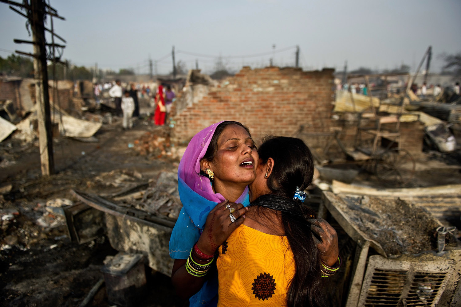 April 12, 2013. Indian slum residents weep as they stand near their burnt shanty in Bawana on the outskirts of New Delhi. A fire broke out in a slum on the outskirts of New Delhi, a local report said, with one person reported dead and another five injured.