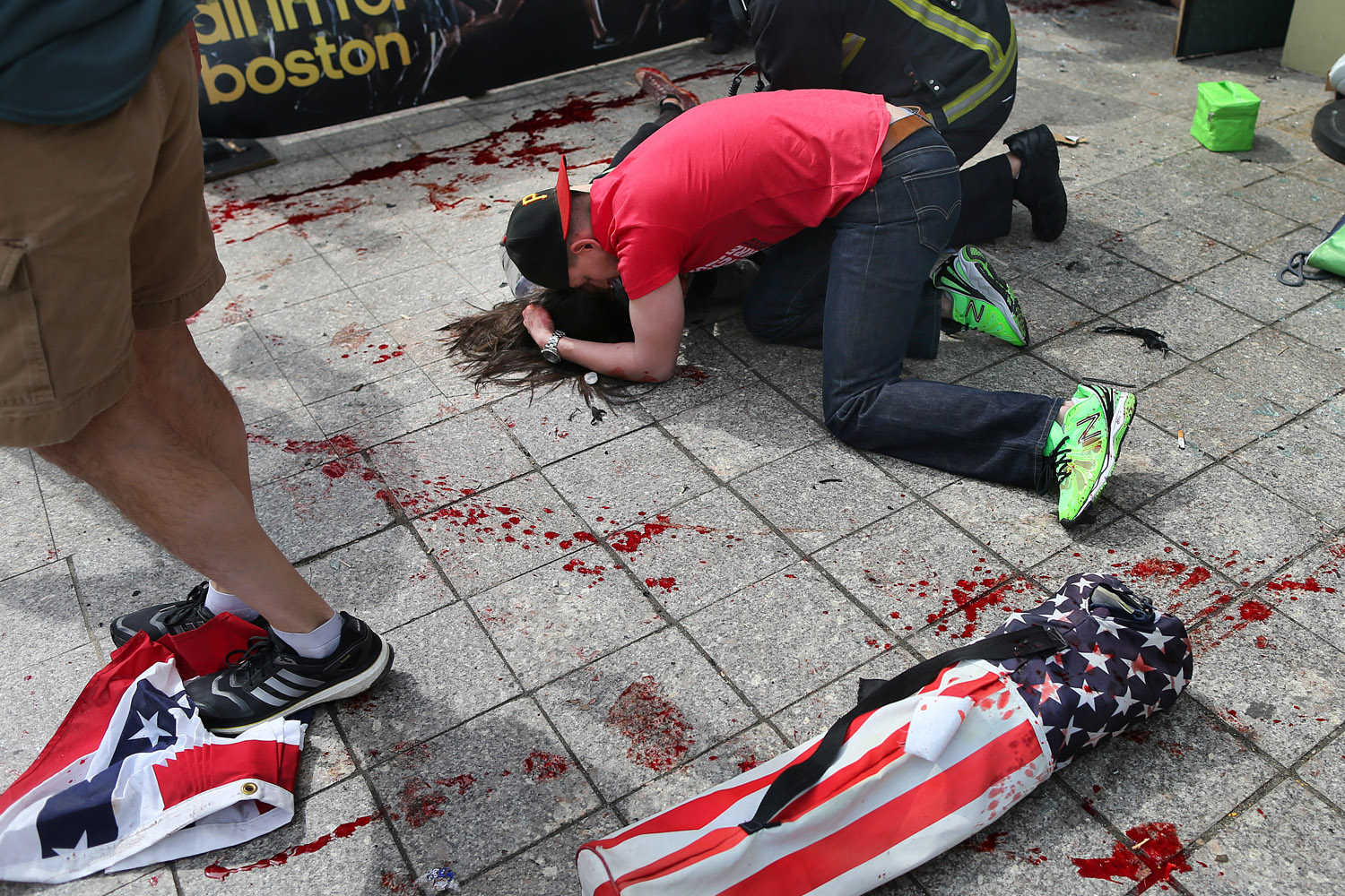 April 15, 2013. A man comforts a victim on the sidewalk at the scene of the first explosion near the finish line of the 117th Boston Marathon.