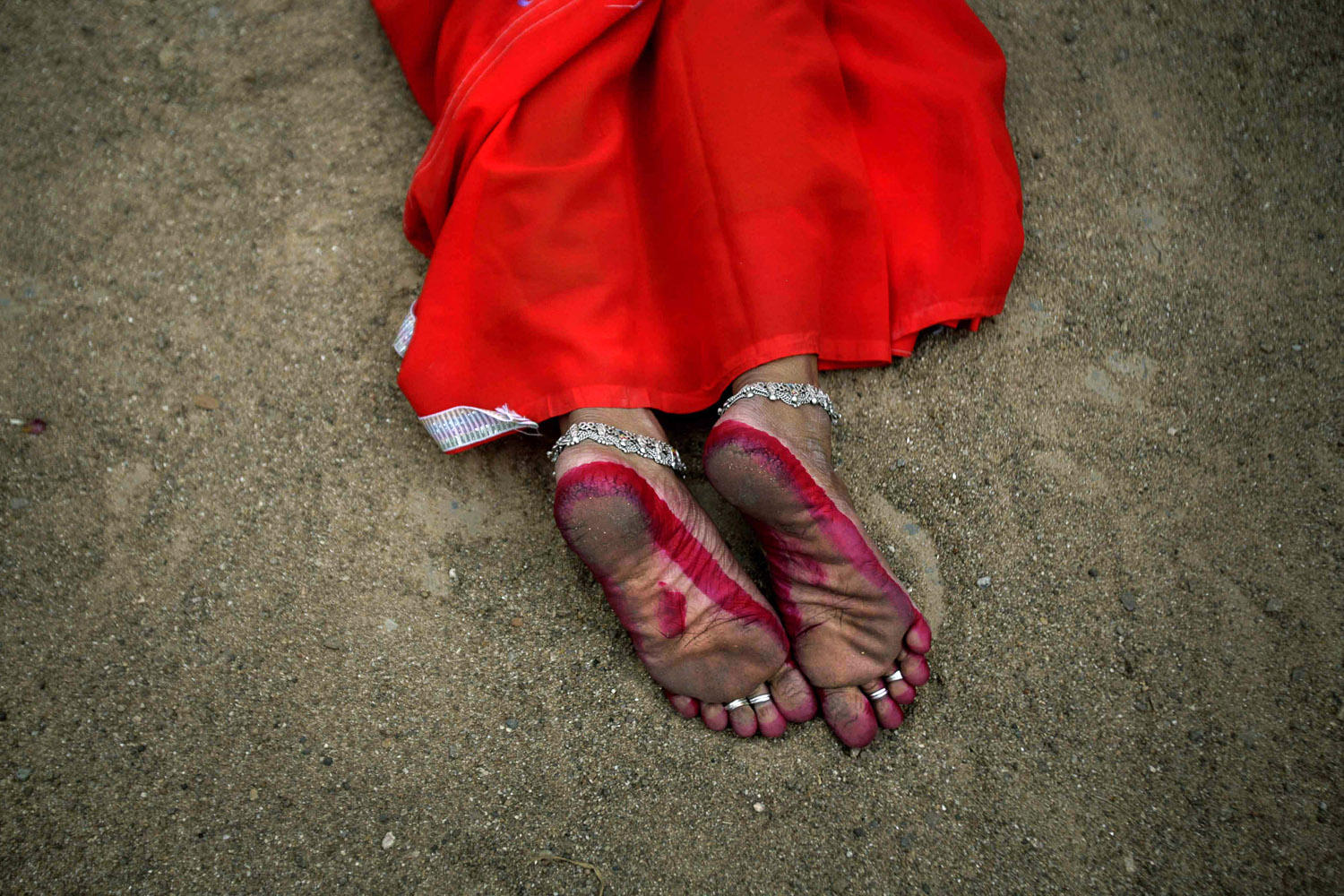 April 2, 2013. A devotee lies on hot sand as a form of penance on the first day of the Danda festival at Kulagarh, in Ganjam district, about 200 kilometers (125 miles) from Bhubaneswar, India.