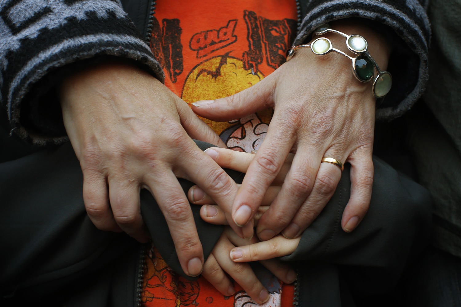 April 21, 2013. A mother holds the hands of her son as they attend an interfaith worship service at a memorial on Boylston Street for the victims of the Boston Marathon bombings in Boston, Massachusetts.