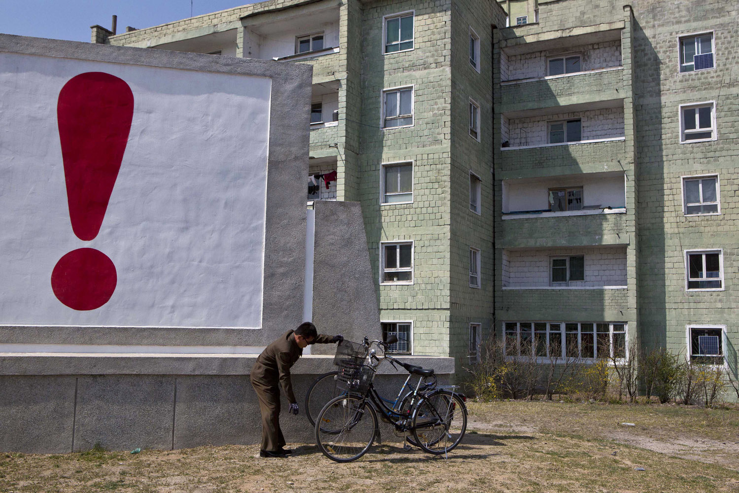 April 24, 2013. A North Korean man checks his bicycle next to a painted exclamation point on a propaganda billboard in Kaesong, North Korea, north of the demilitarized zone which separates the two Koreas.
