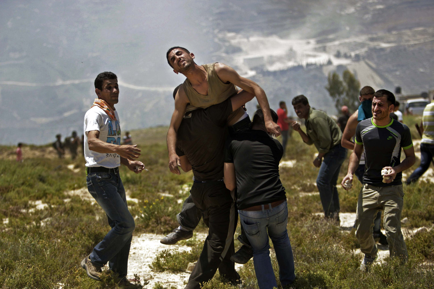 April 30, 2013. Palestinians help a wounded man during clashes with Jewish settlers near the Jewish settlement of Yitzhar, near Nablus.