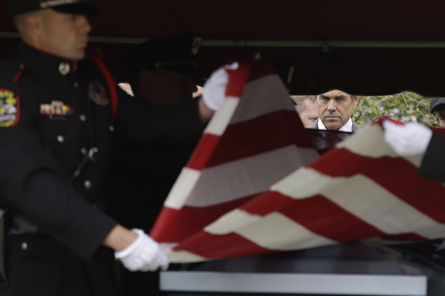 April 4, 2013. Texas Gov. Rick Perry looks on as a flag is folded to present to the family of Kaufman County District Attorney Mike McLelland and his wife, Cynthia after a memorial services in Mesquite, Tx.