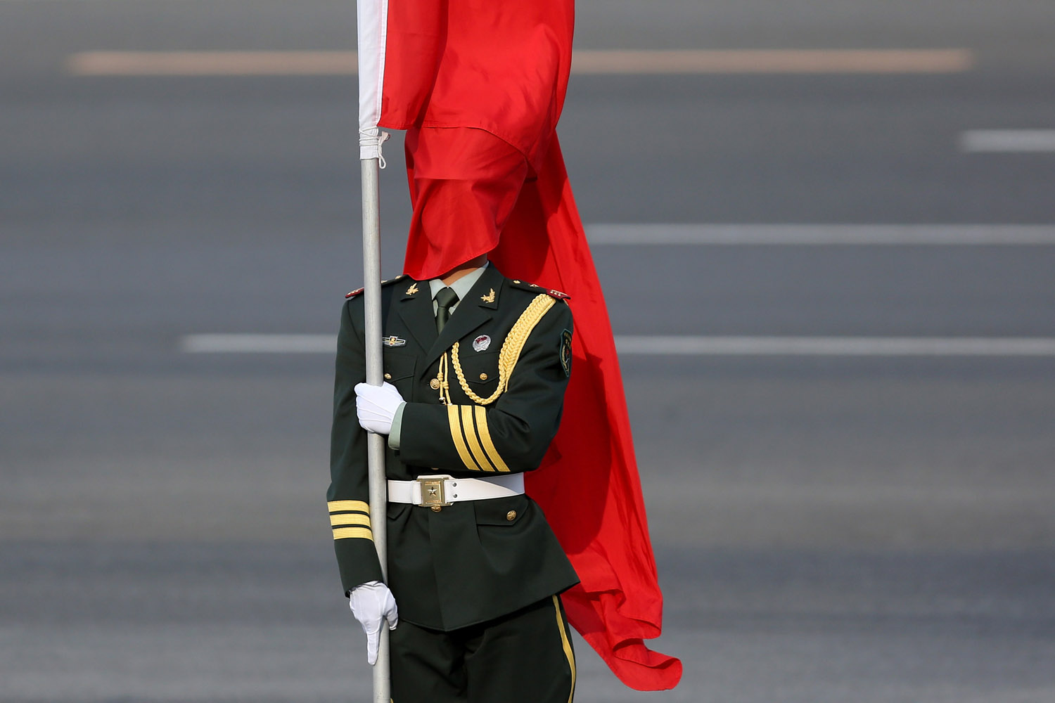 April 9, 2013. The wind blows a red flag onto the face of an honour guard before a welcome ceremony for Australia's Prime Minister Julia Gillard outside the Great Hall of the People in Beijing, China.