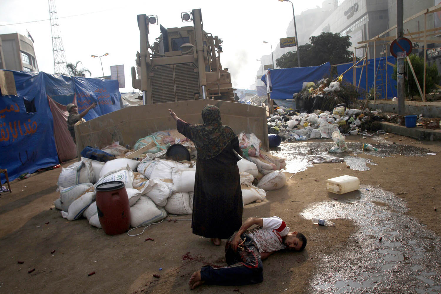 Aug. 14, 2013. An Egyptian woman tries to stop a military bulldozer from hurting a wounded youth during clashes that broke out as Egyptian security forces moved in to disperse supporters of Egypt's deposed president Mohamed Morsi in a huge protest camp near Rabaa al-Adawiya mosque in eastern Cairo.