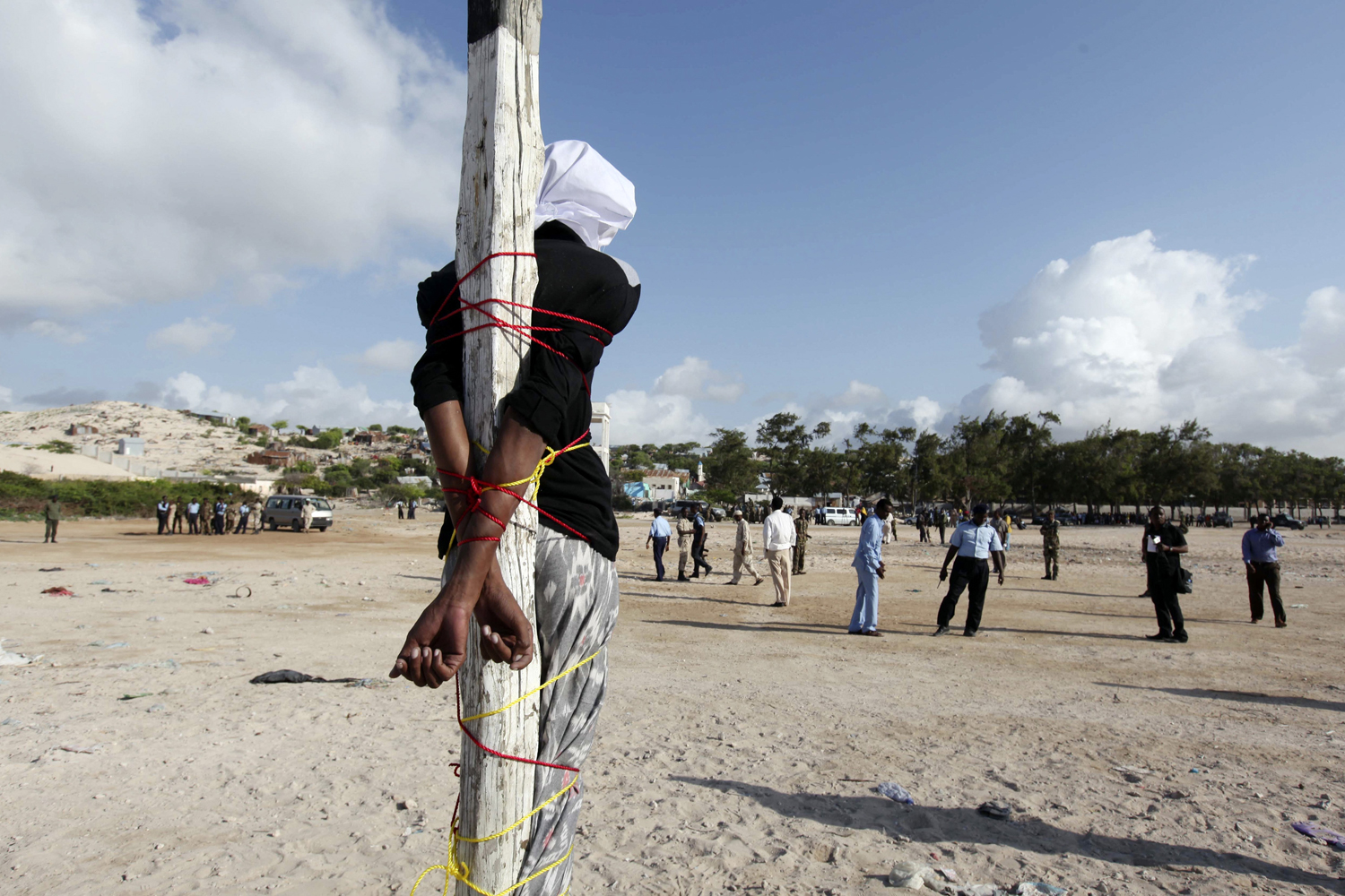 Aug. 17, 2013. Adan Sheikh Abdi Sheikh, who has been sentenced to death for the murder of journalist Hassan Yusuf Absuge, stands tied to a pole before he is executed by shooting at close range at the Iskola Bulisiya square in the capital Mogadishu.