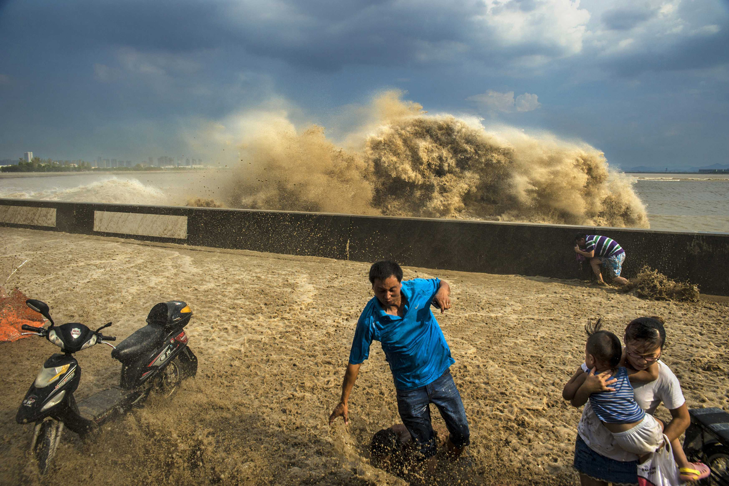 Aug. 24, 2013. Visitors run away as waves from a tidal bore surge past a barrier on the banks of Qiantang River, in Hangzhou Zhejiang province, China.