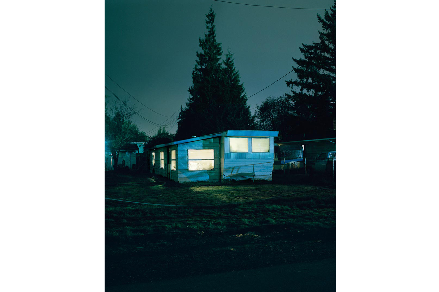Pictured: From the series Excerpts from Silver Meadows #2810                               Date: 1996-2013                                I became aware of Todd's work through his first book House Hunting (Nazraeli Press, 2001). The photographs depict lower middle class homes and small town motels mostly shot at night. There are lights shining from within, and the occassional solitary street light illuminates a dirty pile of snow, a broken down car, a fenced in yard. As viewers, we're neither too close nor too far from the apparent subject. There are no humans depicted in House Hunting.  Over subsequent volumes (Hido has published roughly 6 monographs), portraits of people, mostly women, crept into the work. Excerpts from Silver Meadows is a full-blown masterpiece of  photographic noir, rife with suggestion; place is as much a central character as the women who make appearances and then fade in the rear-view mirror. We are in 'the vicinity of narrative' — a fictional narrative, in my view — without being told the story. —Darius Himes, director of Fraenkel Gallery and co-founder of Radius Books