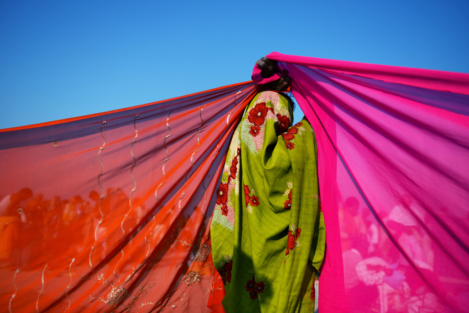 Feb. 10, 2013. An Indian woman holds up the corners of two saris to dry on the banks of the Sangam or confluence of the Yamuna, Ganges and mythical Saraswati rivers at the Kumbh Mela in Allahabad.