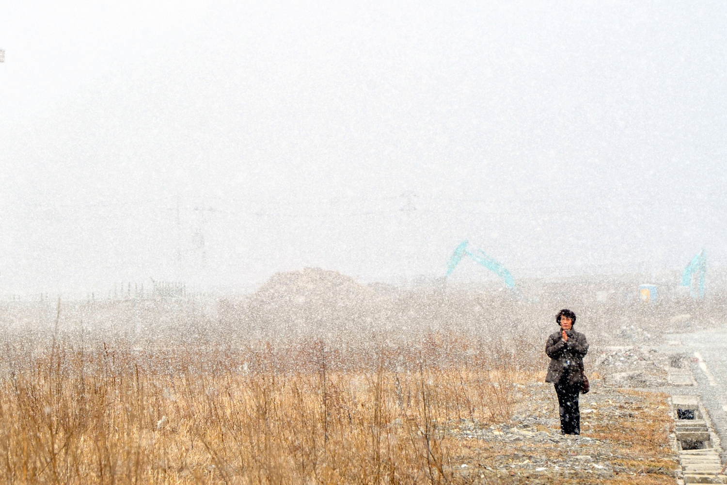 Feb. 11, 2013. A woman stands in the snow and prays towards the former city hall in Minamisanriku, Miyagi, Japan.