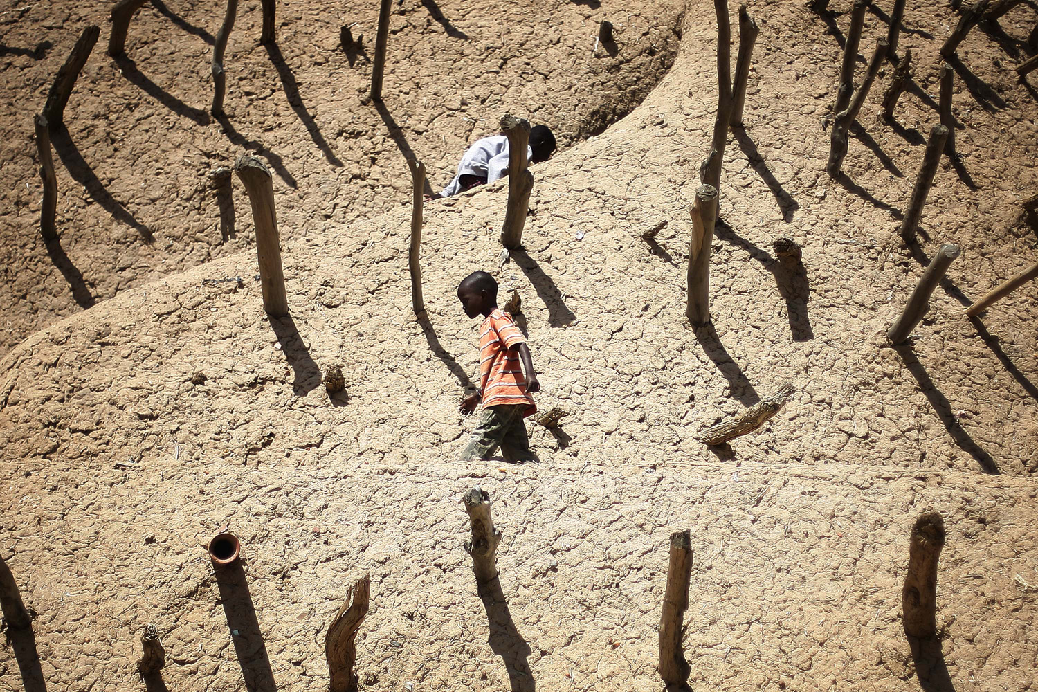 Feb. 15, 2013. Children walk on the Askia mausoleum, built in 1495 in Gao, northern Mali, one week after a suicide bomber on a motorcycle killed himself attempting to blow up an army checkpoint at the entrance of the town.