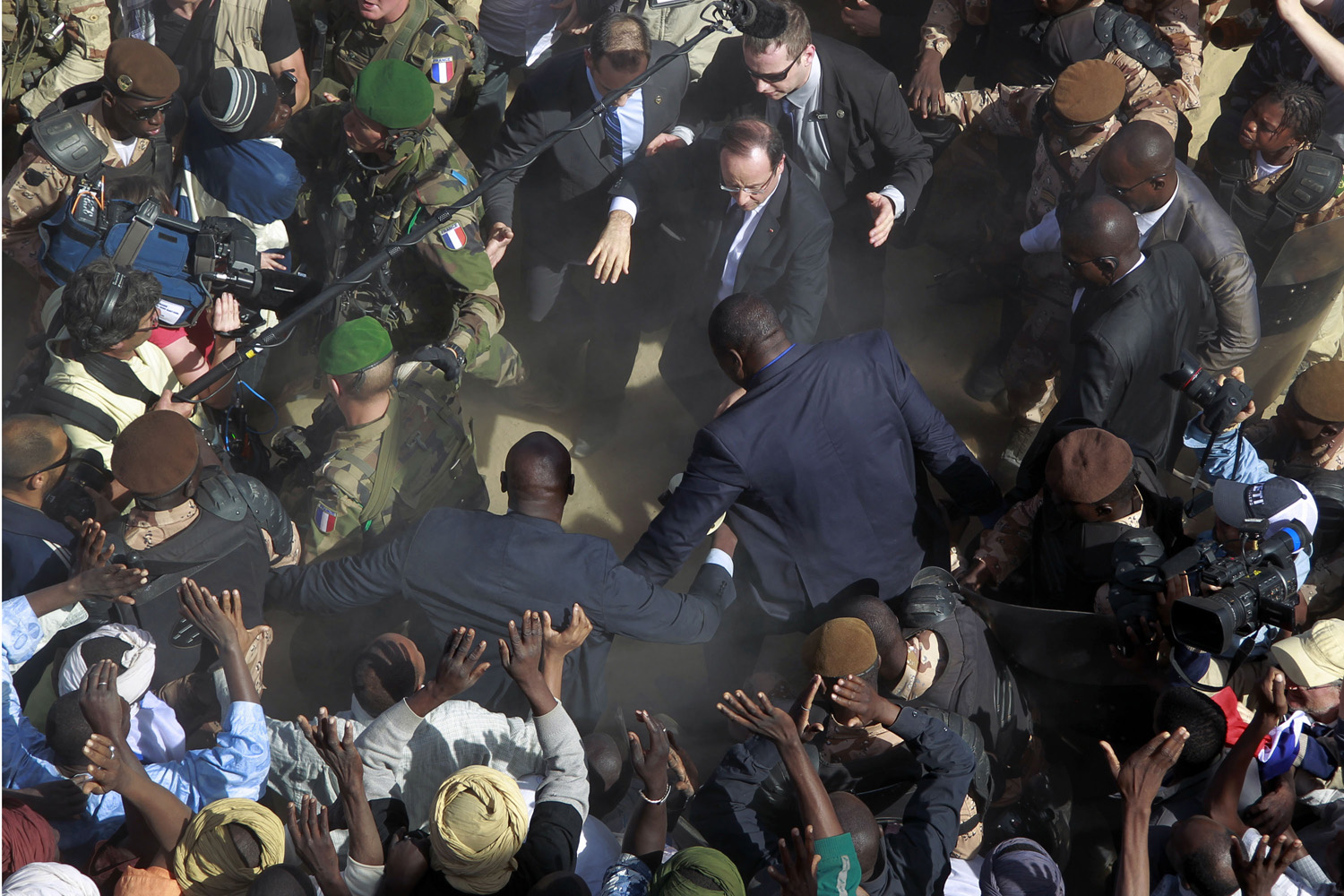 Feb. 2, 2013. French President Francois Hollande, upper center, is surrounded by security as he greets well-wishers during his two-hour-long visit to Timbuktu, Mali.