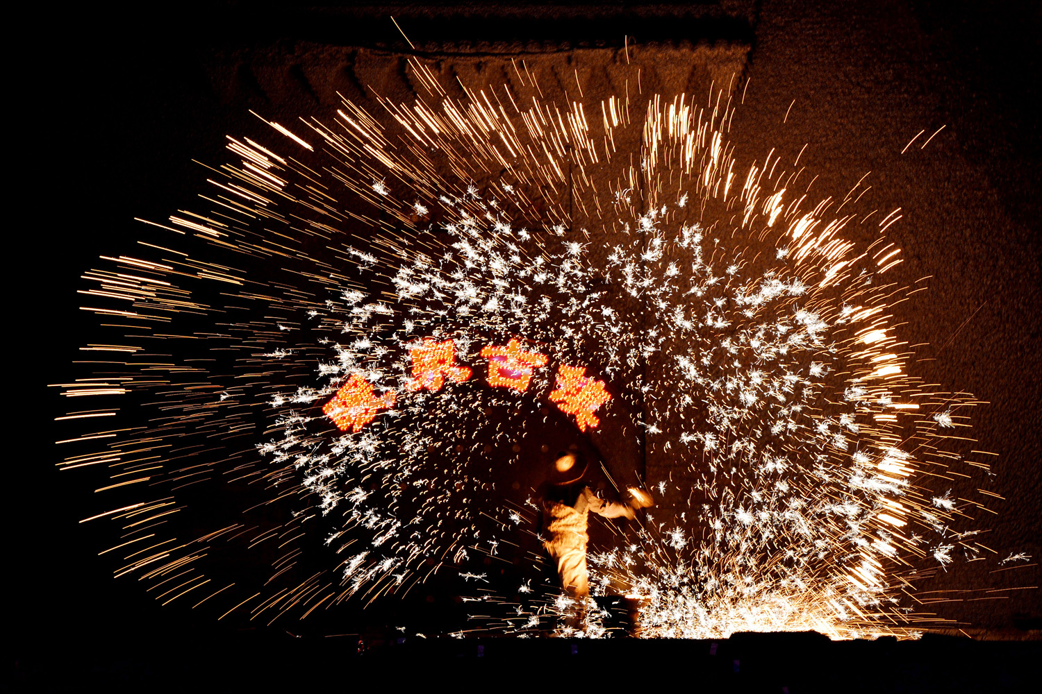 Feb. 24, 2013. A Chinese blacksmith throws molten metal against a cold stone wall to create sparks during the Lantern Festival which traditionally marks the end of the Lunar New Year celebrations, in Nuanquan, Hebei province.