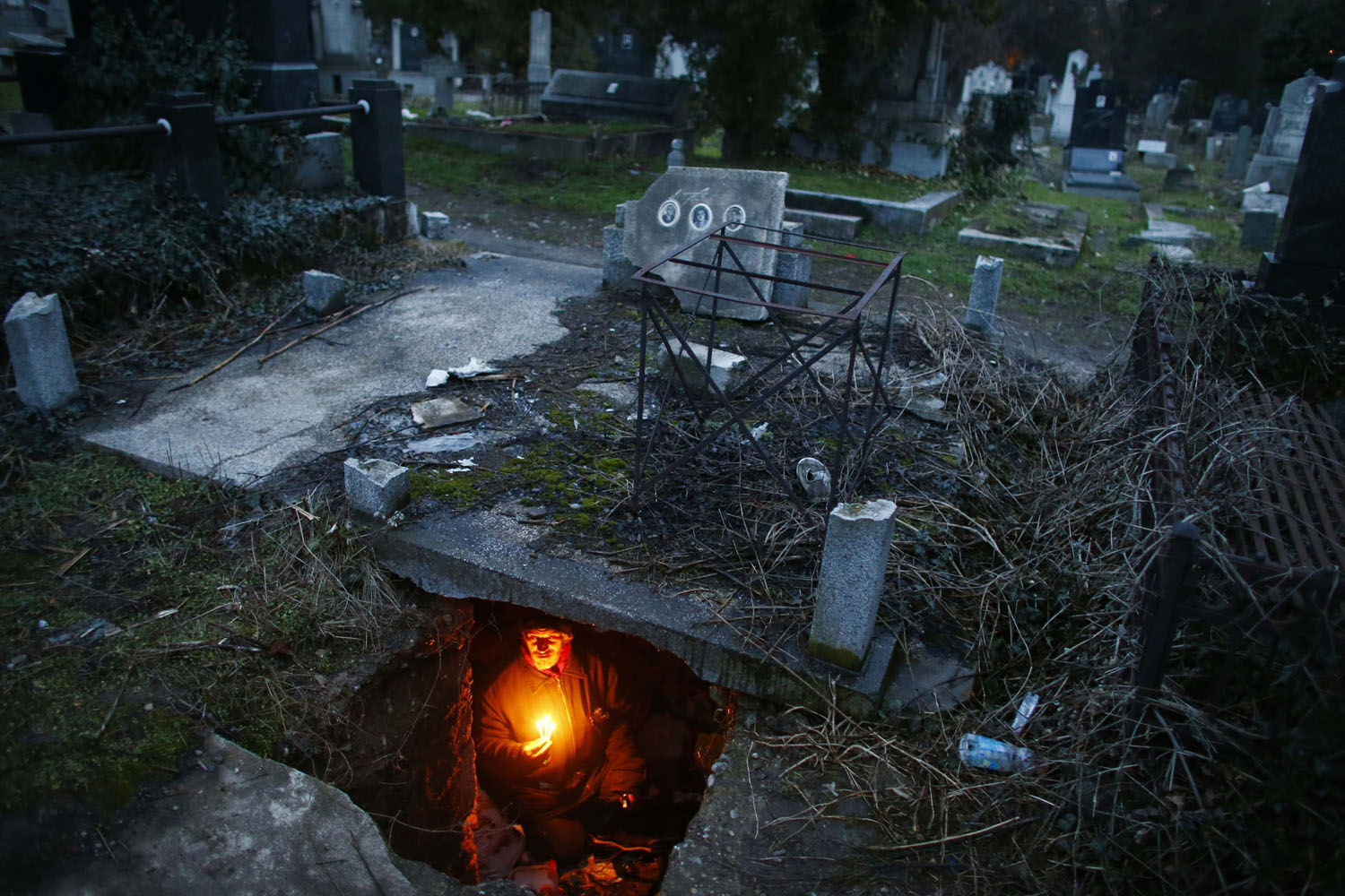 Feb. 9, 2013. Bratislav Stojanovic, a homeless man, holds candles as sits in a tomb where he lives in southern Serbian town of Nis.