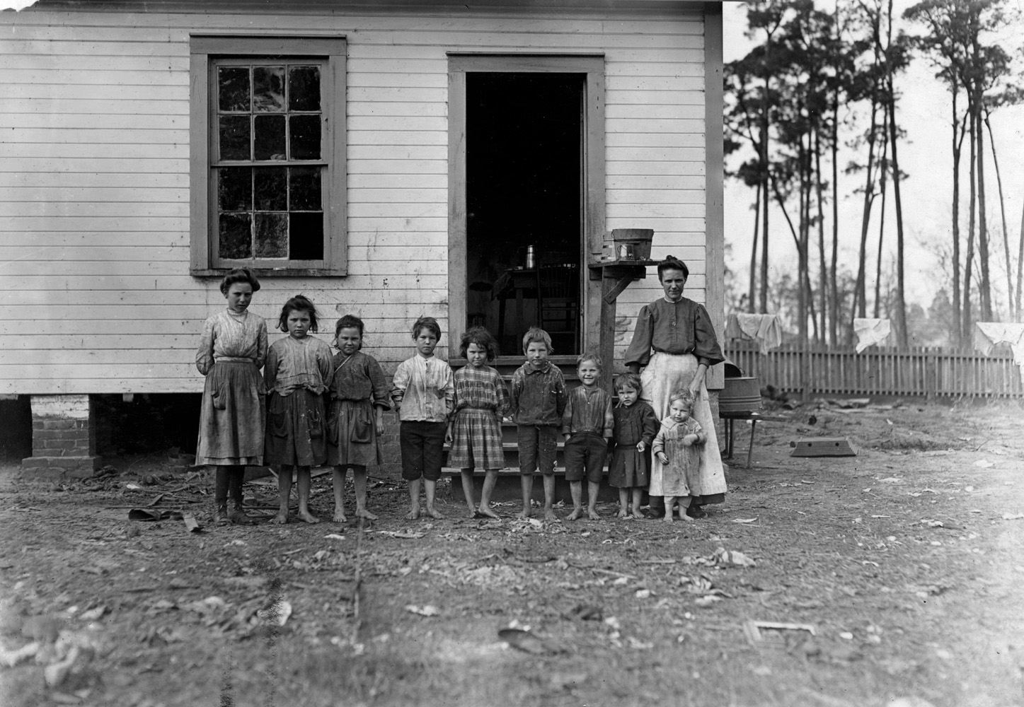 "Catherine Young, widow with nine children, six working in cotton mill, Tifton, Georgia, 1909.                                A family working in the Tifton (Ga.) Cotton Mill. Mrs. A.J. young works in mill and at home. Nell (oldest girl) alternates in mill with mother. Mammy (next girl) runs 2 sides. Mary (next) runs 1 1/2 sides. Elic (oldest boy) works regularly. Eddie (next girl) helps in mill, sticks on bobbins. Four smallest children not working yet. The mother said she earns $4.50 a week and all the children earn $4.50 a week. Husband died and left her with 11 children. 2 of them went off and got married. The family left the farm 2 years ago to work in the mill. January 22, 1909.  —Hine's original caption                               ""My mother told me about the day she and her brothers and sisters went to the orphan's home, and how she was crying. She said she had helped with the baby all day, and then she never saw her again. I told my Mama that her mother had no choice, because there wasn't any way they could make a living. So that's when she gave them away."" —Daughter of one of the Young children"
