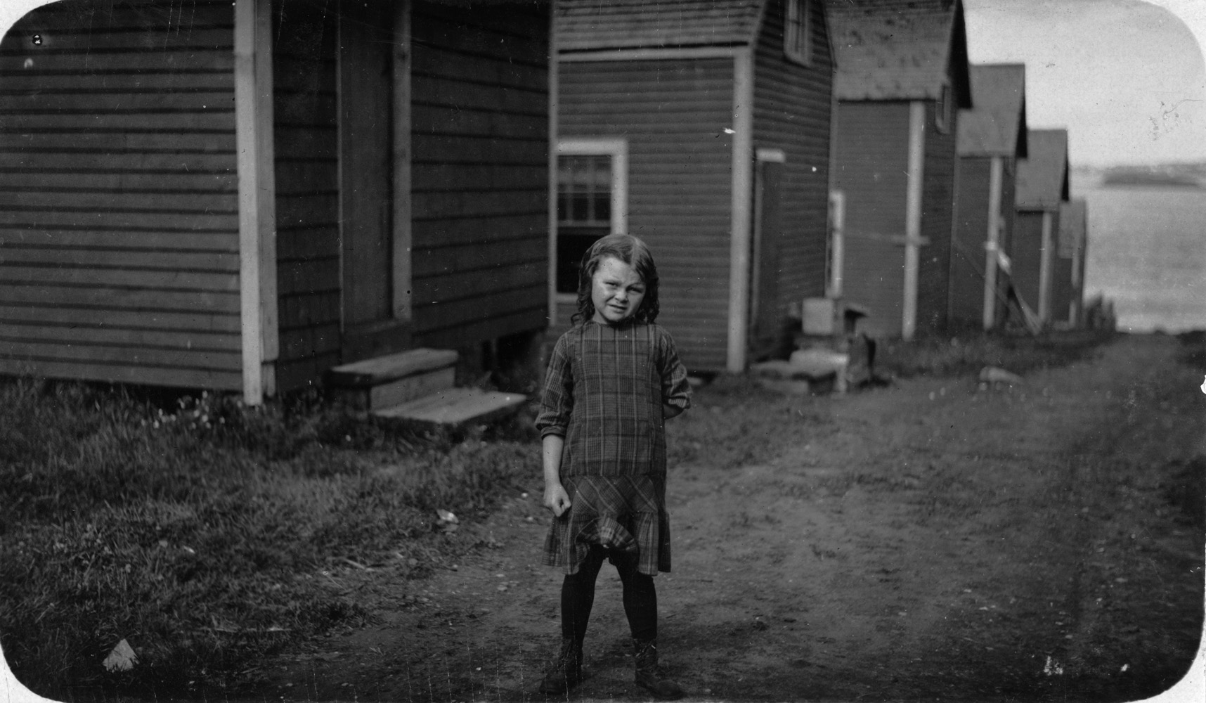 "Elsie Shaw, fish cannery worker, six years old, Eastport, Maine, 1911. Elsie Shaw, a 6 year old cartoner during the summer, Seacoast Canning Co., Factory #2. Her father is boss of cutting room in Factory #1. He asked me to take some photos of her, as he has her do a singing act in vaudeville in the winter,  and she's old enough now to go through the audience and sell her own photos.  —Hine's original caption ""Nana loved to talk about the days when she was in vaudeville as a young child. She would tell me stories about performing on stage, singing and dancing and doing little skits."" —Granddaughter of Elsie Shaw"