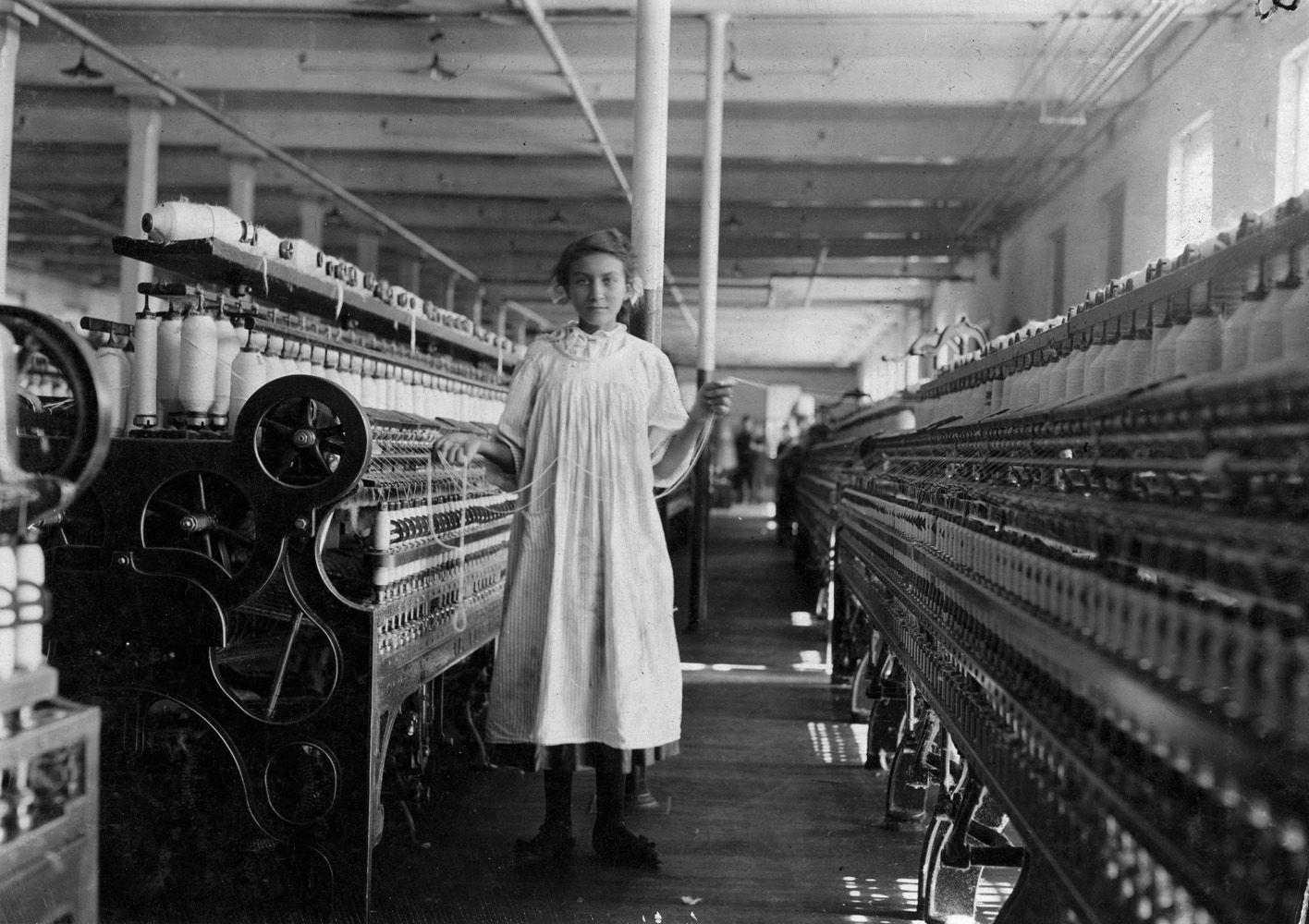 "Mamie Laberge, cotton mill worker, 13 years old, Winchendon, Massachusetts, 1911. Mamie La Barge at her Machine. Under legal age.  —Hine's original caption ""She was a soft, caring, comforting grandmother. She loved to be around her grandchildren. She was a hard worker. She was always cleaning the house. She was well groomed, always wore a dress, and made you proud that she was your grandmother."" —Granddaughter of Mamie Laberge"