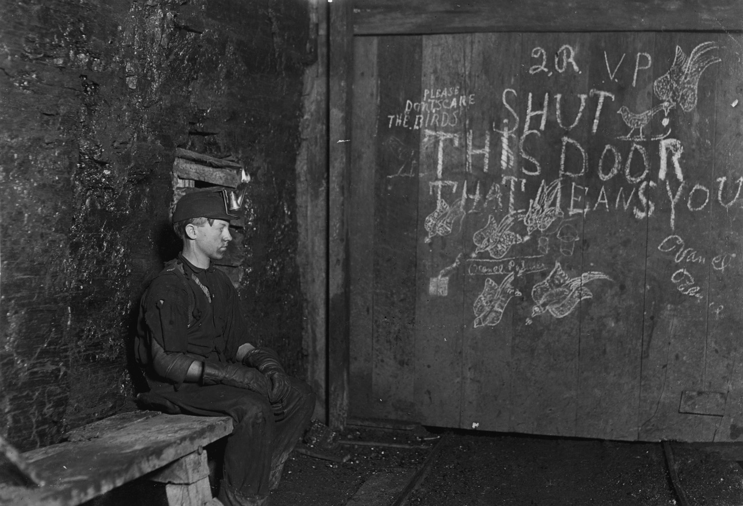"Vance Palmer, trapper boy in coal mine, about 15 years old, Harrison County, West Virginia, 1908. Has trapped for several years in a West Va. Coal mine. $.75 a day for 10 hours work. All he does is to open and shut this door: most of the time he sits here idle, waiting for the cars to come. On account of the intense darkness in the mine, the hieroglyphics on the door were not visible until plate was developed.  —Hine's original caption                                                              ""I knew he had to work when he was young, but I didn't know he worked at the mine. I remember him telling me that he went down in the mines once and said he would never work there."" —Son of Vance Palmer"