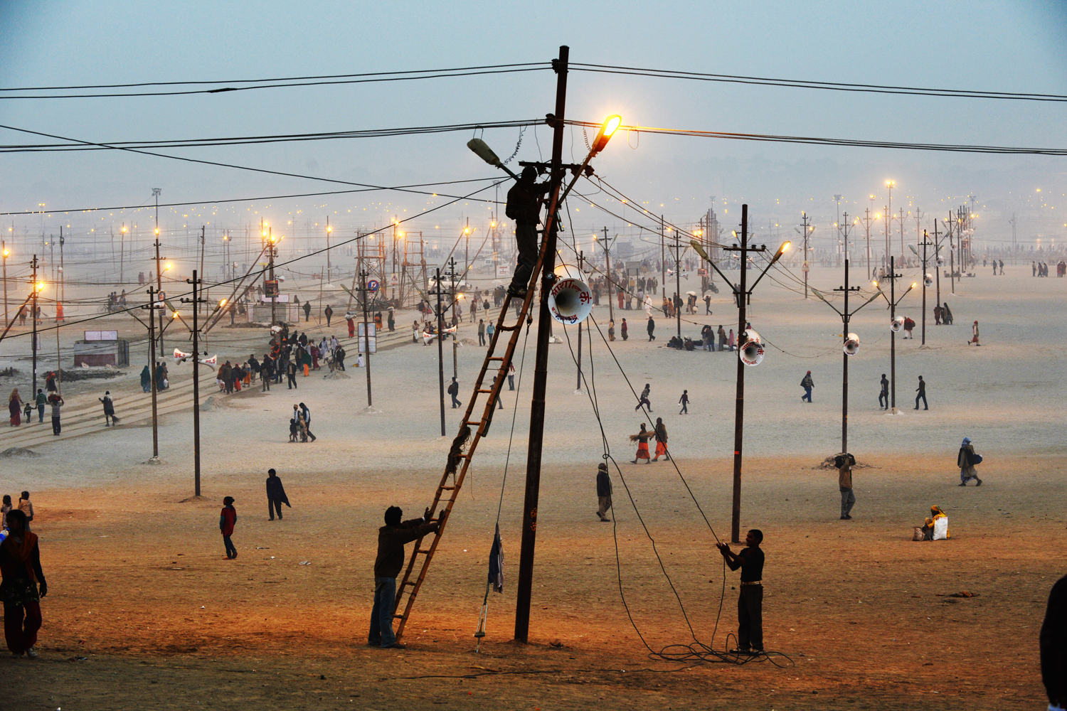 Jan. 13, 2013. Workers fix a lightpost, one of many that will illuminate the vast grounds receiving the millions of Hindu devotees that will congregate here for the next couple of months to celebrate the Kumbh Mela, in Allahabad, India.