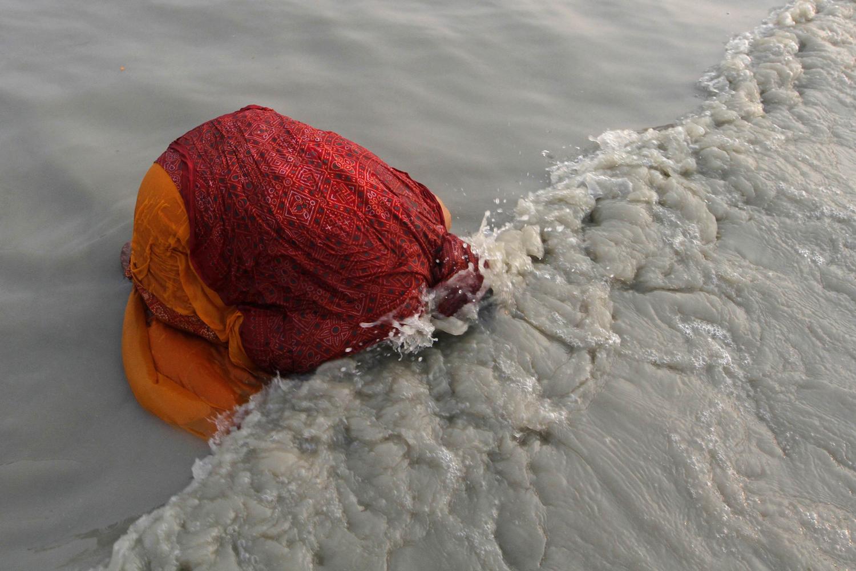 Jan. 14, 2013. A female Hindu pilgrim takes a dip at the confluence of the Ganges river and the Bay of Bengal at Sagar Island, south of Kolkata, India.