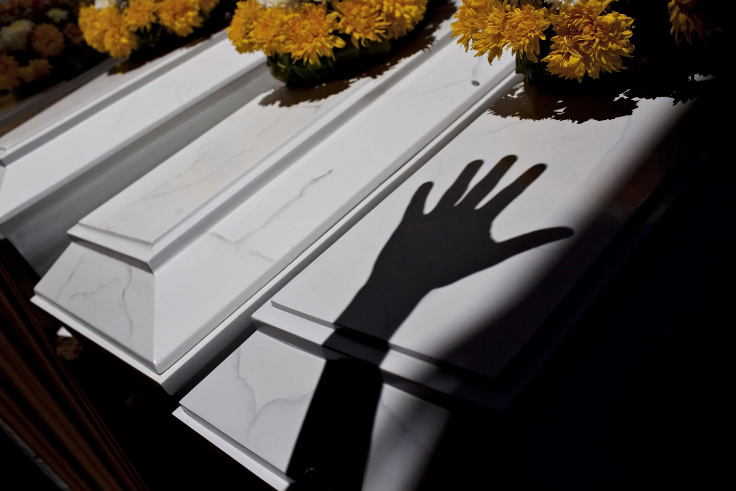 Jan. 25, 2013. The shadow of a relative's hand is projected onto the coffins of victims, killed in massacres executed by Shining Path militant group and the army in Peru's southern district of Chungui between 1984 and 1985, during a funeral ceremony in Ayacucho city.
