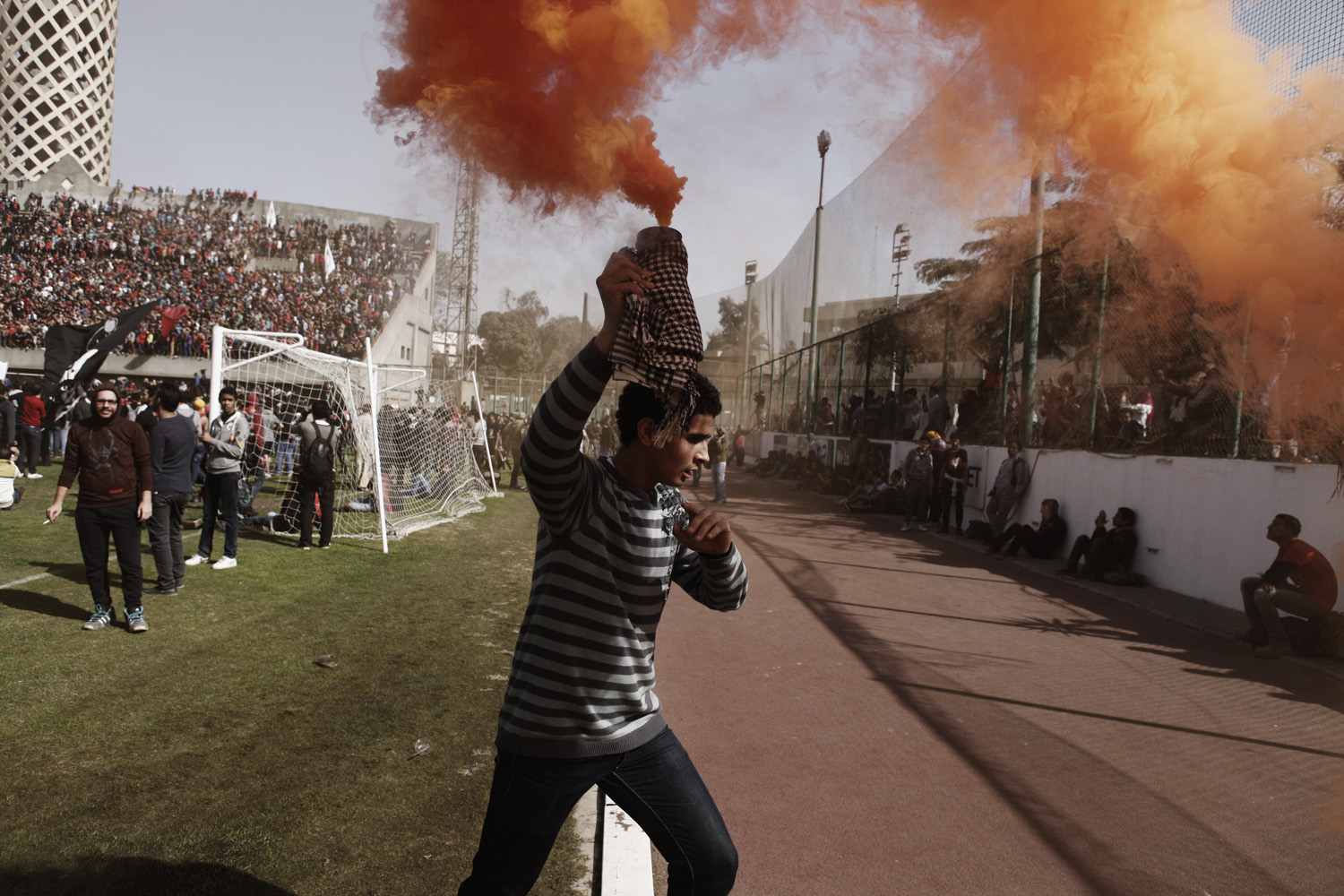 Jan. 26, 2013. An Egyptian 'Ahly Ultra' soccer fan holds a smoke flare above his head during celebrations after the announcement that 21 fans of the Al Masry football club involved in a football stadium massacre last year were sentence to death in Cairo, Egypt.