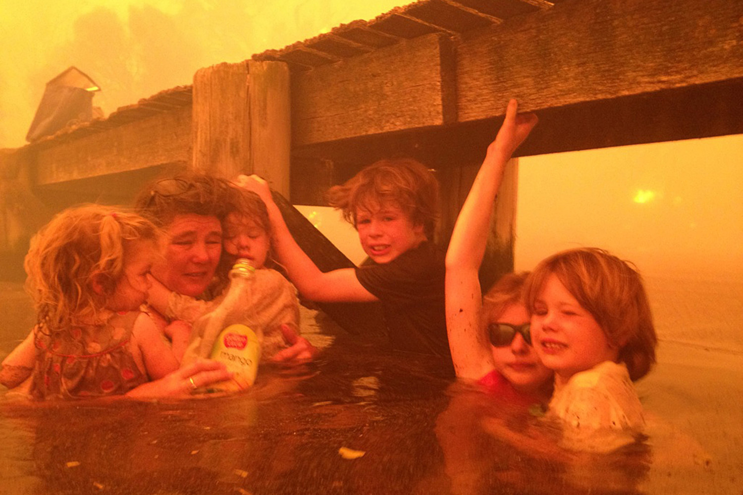 Jan. 4, 2013. Tammy Holmes, second from left, and her grandchildren, two-year-old Charlotte Walker, left, four-year-old Esther Walker, third from left, nine-year-old Liam Walker, eleven-year-old Matilda, second from right, and six-year-old Caleb Walker, right, take refuge under a jetty as a wildfire rages near-by in the Tasmanian town of Dunalley, east of the state capital of Hobart, Australia.