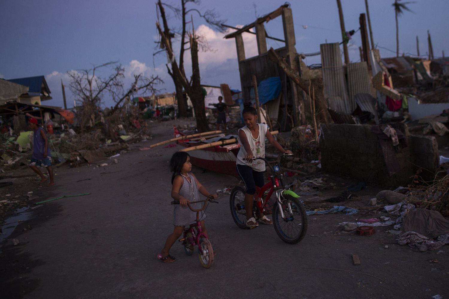 A woman and child bicycle through the rubble of homes destroyed by Haiyan in Tanuan, Nov. 15, 2013.