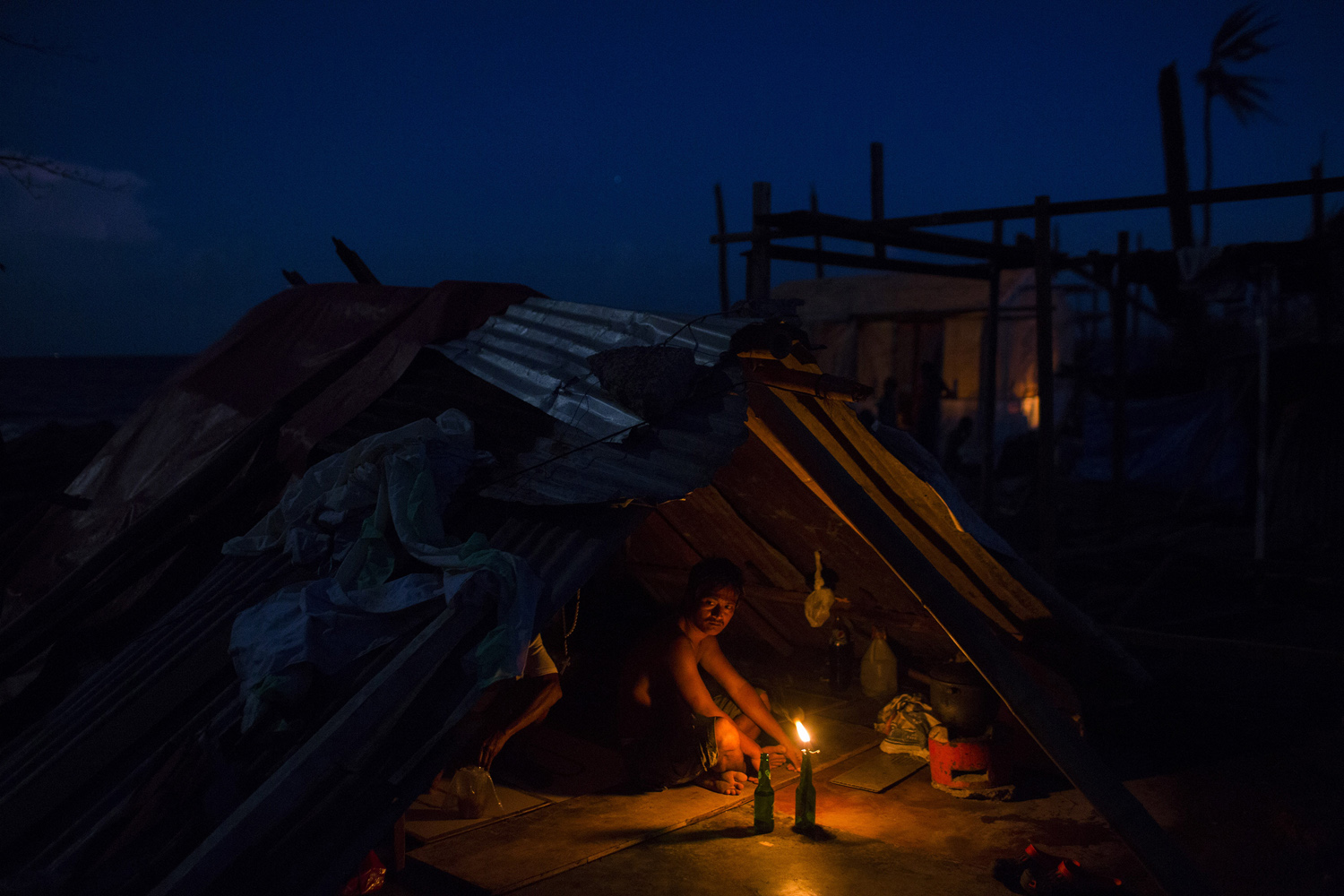 A man whose home was destroyed by Haiyan sits in the rubble of his home in Tanuan, Nov. 15, 2013.