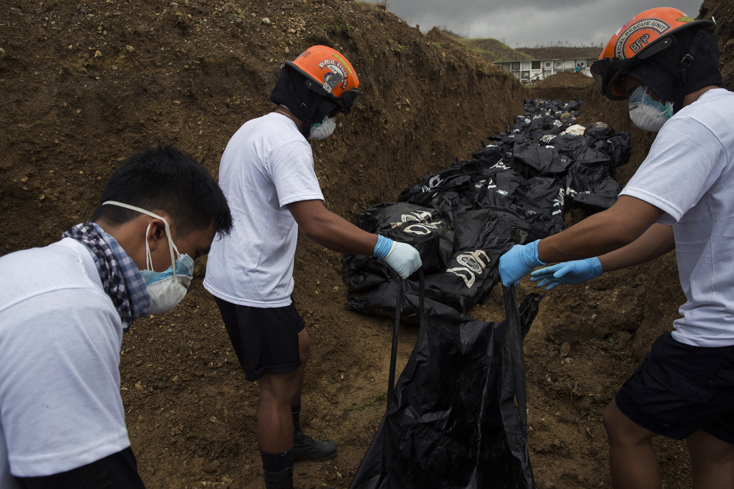 Rescue workers load body bags of people killed by Haiyan into a mass grave in Tacloban, Nov. 16, 2013.