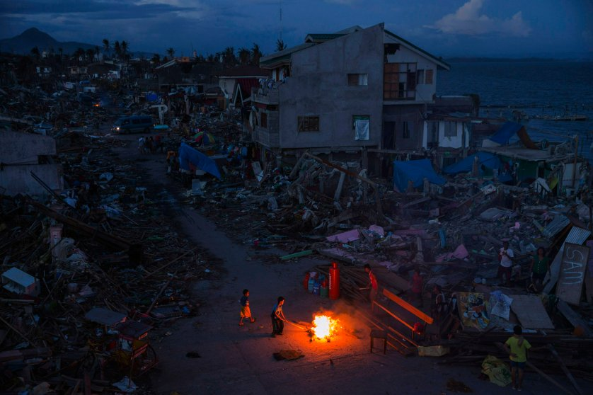 People play by a fire in a neighbourhood destroyed by Haiyan Typhoon in Tacloban, The Philippines on November 16, 2013.