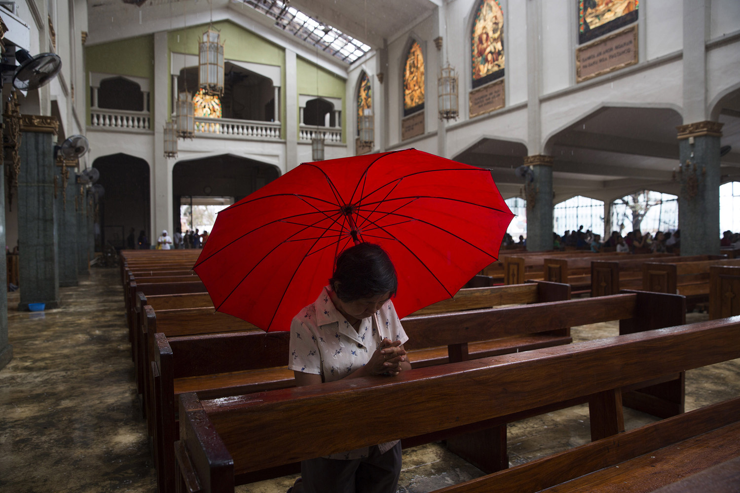 A woman prays with an umbrella to protect her from the rain falling through the damaged roof of the Santo Nino church in Tacloban, Nov. 17, 2013.