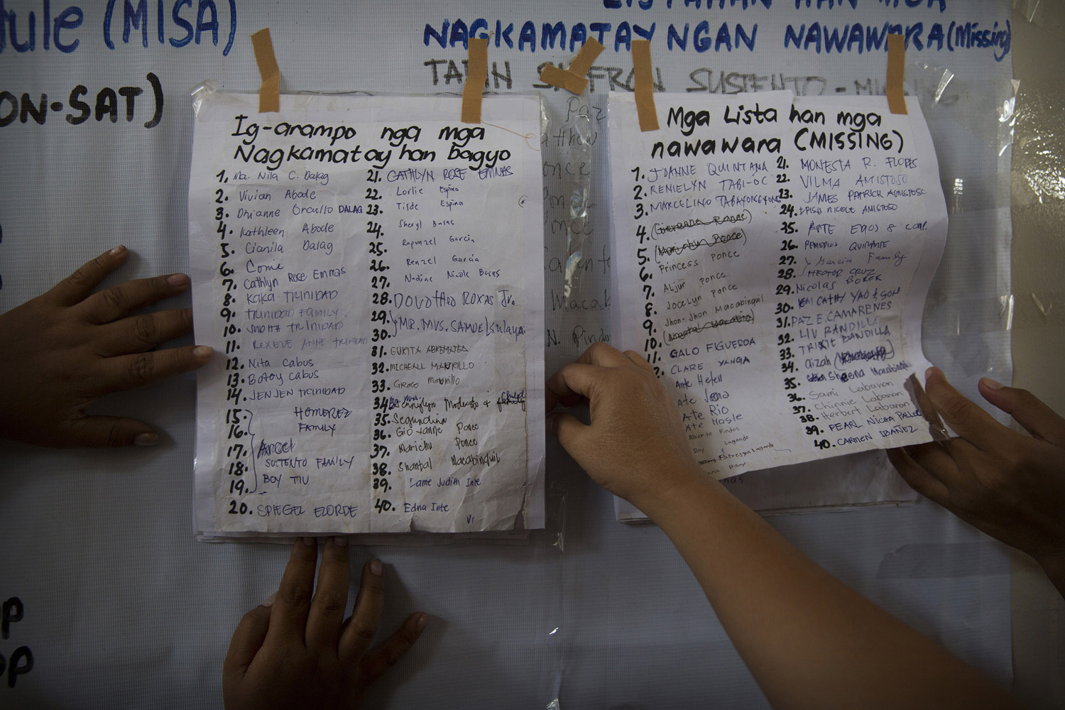 Relatives search a list of missing persons posted in Tacloban on Nov. 17, 2013.