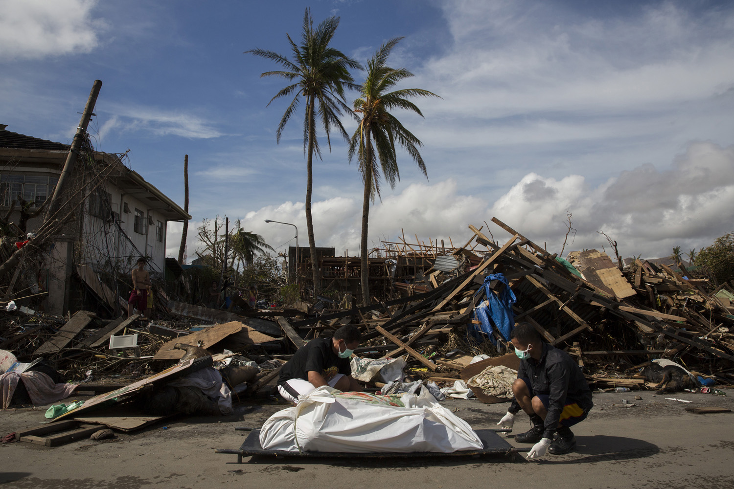 Men remove the body of a woman killed in Tacloban, Nov. 13, 2013.