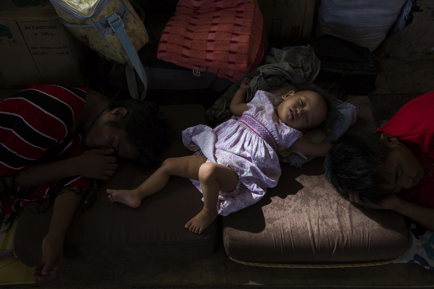 A girl sleeps in a church being used as a shelter for those made homeless by the storm, Nov. 13, 2013.
