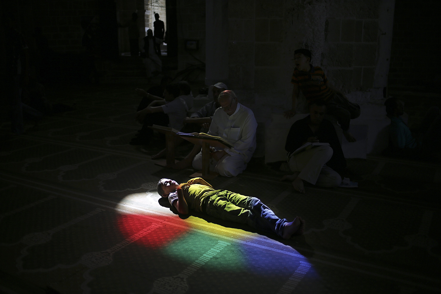 July 11, 2013. A Palestinian child rests as others pray and read the Quran in a mosque during the holy month of Ramadan in Gaza City.