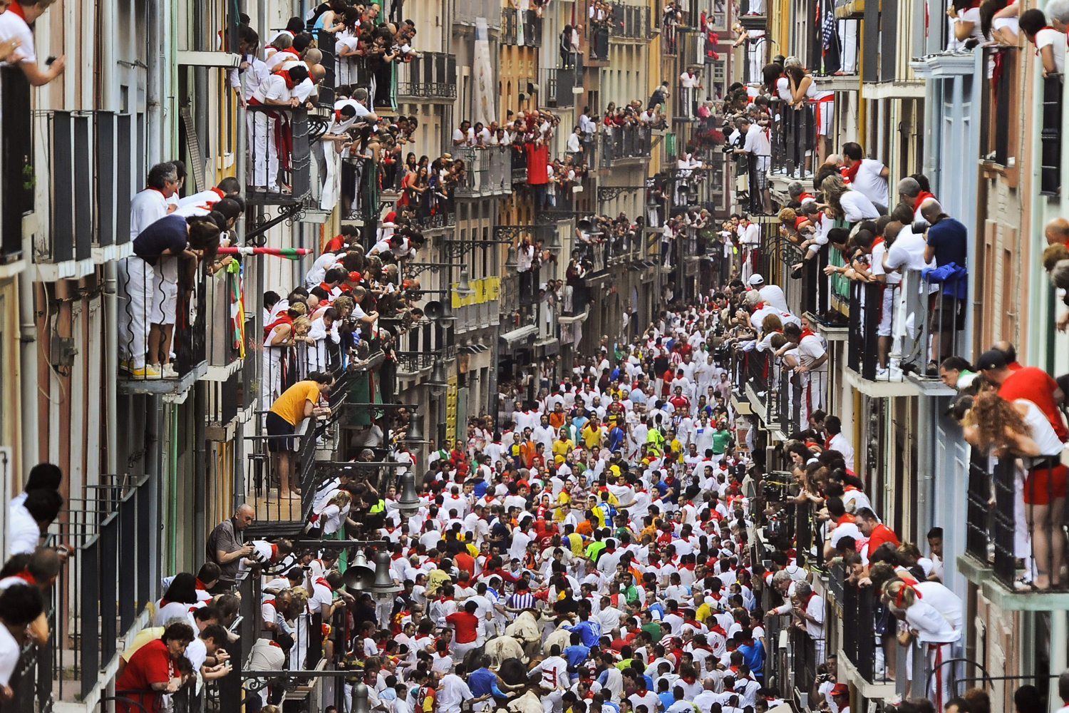 July 12, 2013. Runners make their way through the street with  El Pilar  fighting bulls watched by people from their balconies during the running of the bulls at the San Fermin festival, in Pamplona, Spain.